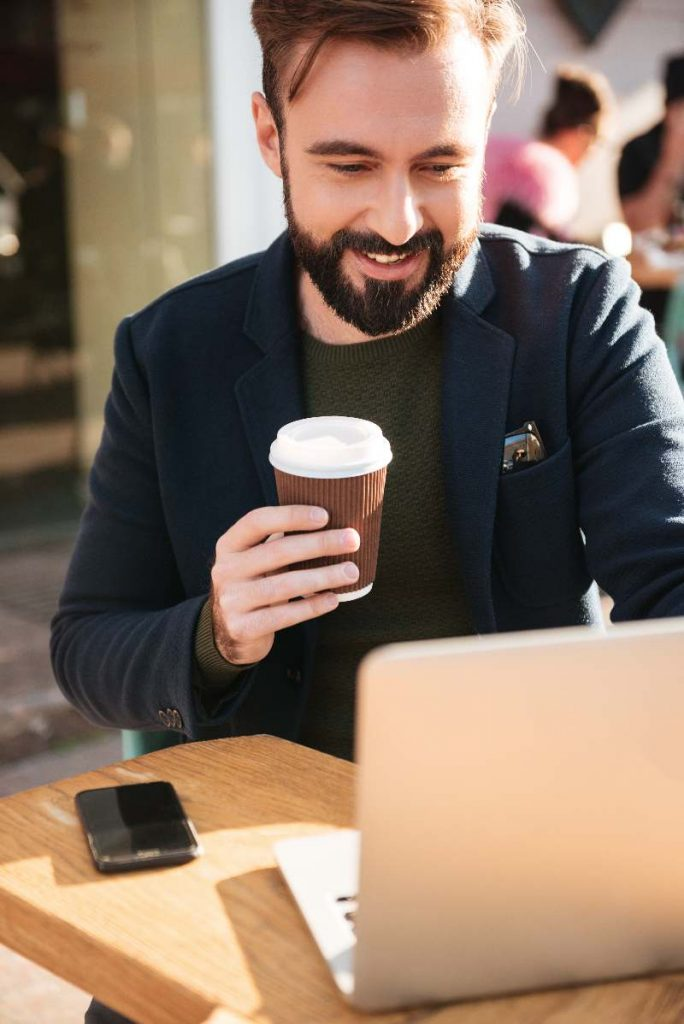 Man working on computer with coffee